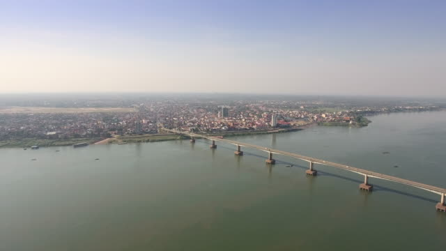 Drone flight backwards revealing a long bridge across the Mekong river, with asian town as backdrop Drone flight backwards revealing a long bridge across the Mekong river, with asian town as backdrop back to back stock videos & royalty-free footage