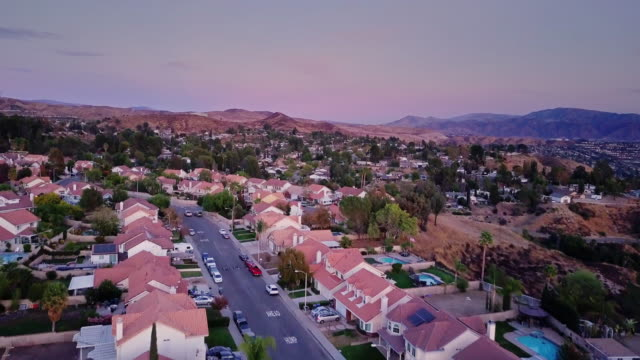 drone flight down suburban street - edificio residenziale video stock e b–roll