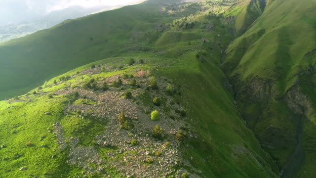 Drone flight in the highlands past the mountain peaks in the summer. Green fields, clear sky.Drone flight in the highlands past the mountain peaks in the summer. Green fields, clear sky.