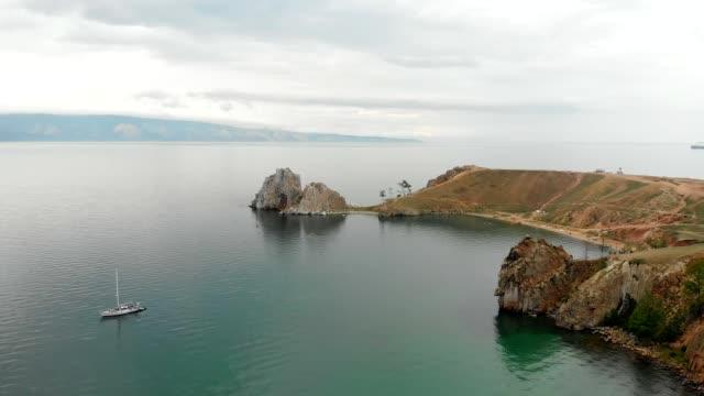 vídeos de stock e filmes b-roll de drone flight over cliff and bay olkhon island on lake baikal, russia. - lago baikal