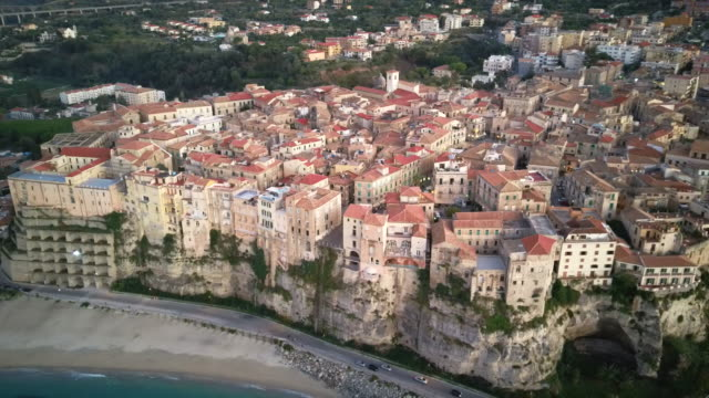 drone flight over houses located on a rock near the coastline calabria - video di tropea video stock e b–roll