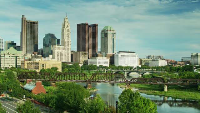 columbus, ohio downtown skyline doğru lush yeşil yaprakları over drone uçuş - columbus day stok videoları ve detay görüntü çekimi