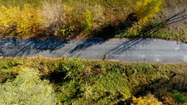 drone flight over the meadow and old asphalt road on a sunny day. - top filmów i materiałów b-roll