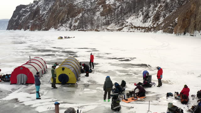 テントでキャンプし、氷の上で眠る準備をしている観光客の上にドローン飛行。 - シベリア点の映像素材/bロール