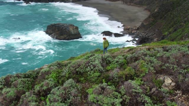vídeos de stock e filmes b-roll de drone flight over woman walking along ridge in big sur - big sur