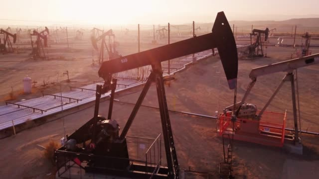 drone flight past working pumpjack in midway-sunset oil field, kern county, california - ископаемое топливо стоковые видео и кадры b-roll