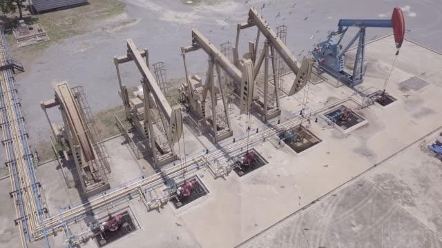 無人機飛行過去工作泵口油泵千斤頂工作和抽運原油的化石燃料能源與鑽井平臺在油田 - 伊朗 個影片檔及 b 捲影像