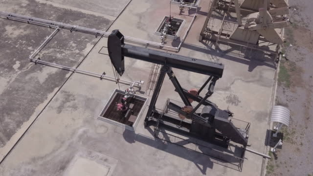 drone flight past working pumpjack ndustrial oil pump jack working and pumping crude oil for fossil fuel energy with drilling rig in oil field - paesi del golfo video stock e b–roll