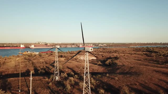 Drone fly near the wings of wind generator on the hill energy farm