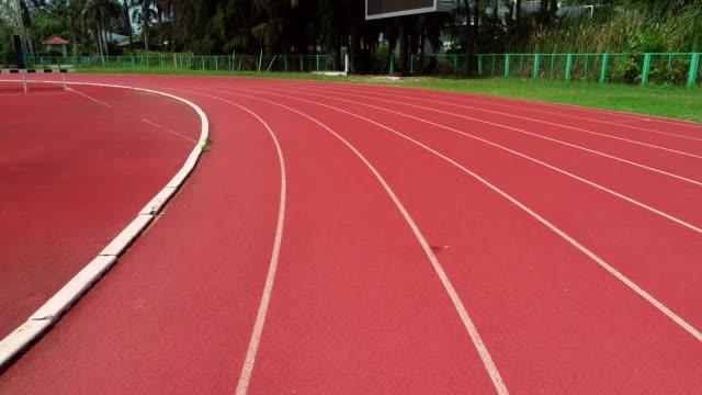 beyaz çizgiler ile bahar stadyumu kırmızı koşma parça üzerinde sinek robot, atış robot. - pist stok videoları ve detay görüntü çekimi