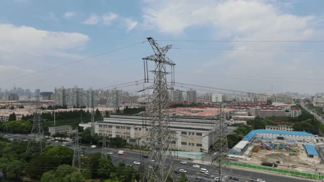 Drone fly up along the electricity pylons with cityscape in Shanghai China