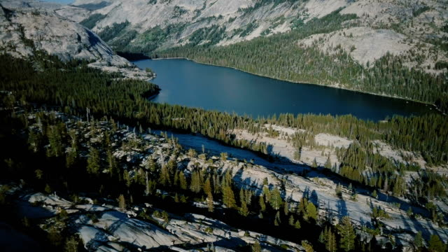 drone flying above amazing white rocky ridge landscape to reveal large mountain lake at summer yosemite national park. - park narodowy yosemite filmów i materiałów b-roll