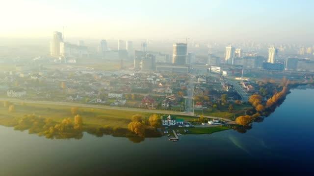 drohne fliegt über große sonnenuntergang stadtlandschaft, verschiedene gebäude in der nähe von schönen noch seeufer und gelbe herbstbäume. - weißrussland stock-videos und b-roll-filmmaterial