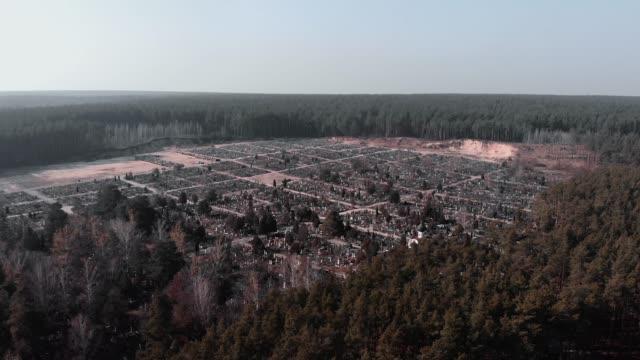 vídeos y material grabado en eventos de stock de drone volando sobre el cementerio rodeado de bosque. disparo aéreo del cementerio. vista superior del cementerio. el dron vuela sobre el cementerio local del pueblo. - árboles genealógicos