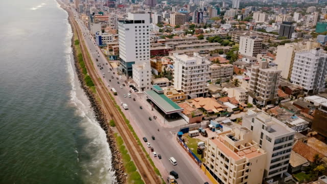Drone flying above Colombo coast, Sri Lanka. Amazing aerial view of city street traffic, modern buildings and ocean Drone flying above Colombo coast, Sri Lanka. Amazing aerial view of city busy street traffic, modern buildings and hotels, small railroad line and beautiful ocean shore on a sunny summer day. colombo stock videos & royalty-free footage