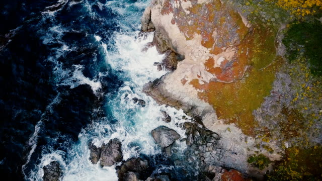 drone che vola sopra l'incredibile costa rocciosa del mare, le onde blu si infrangono su grandi scogliere nel soleggiato scenario del big sur in california. - armonia video stock e b–roll