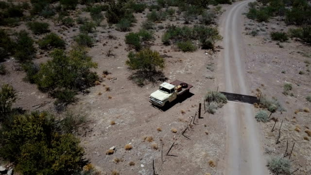 Drone flying above lonely abandoned vintage pickup truck near sandstone gravel desert road, lost in summer USA heat.
