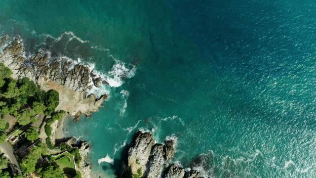 drone flyger över turkost vatten. klippig kust - spain solar bildbanksvideor och videomaterial från bakom kulisserna