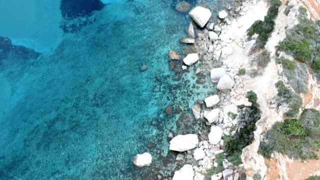 Drone flying above turquoise water. Rocky coastline Aerial view of rocky coastline coastal feature stock videos & royalty-free footage