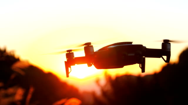 Drone flying against orange sunset Drone flying against orange sunset hovering stock videos & royalty-free footage