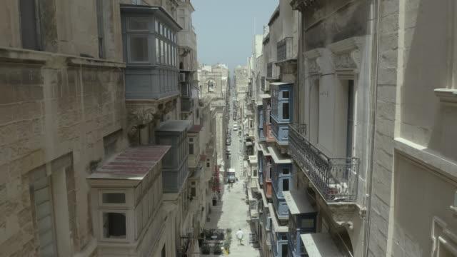 Drone flying back through beautiful old street,Valletta,Malta . Old, vintage windows, balconies. - 4K