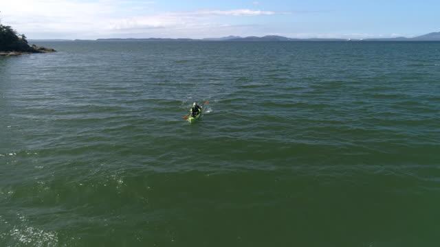 Drone Flying Backwards Facing Man Paddling Kayak in Green and Blue Ocean Water video