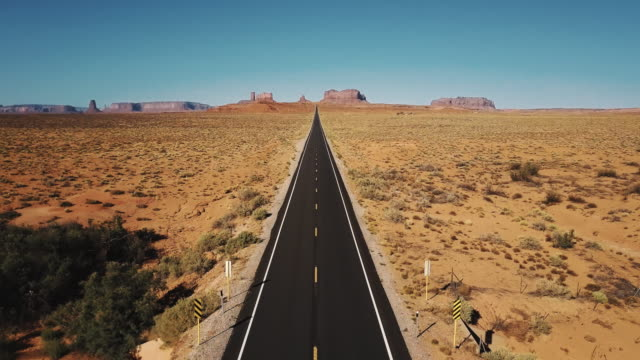 vídeos de stock e filmes b-roll de drone flying backwards over iconic empty sandstone desert road in monuments valley, arizona with big cliff mountains. - eternidade