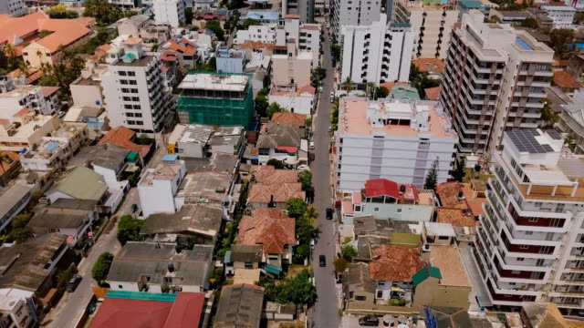 Drone flying backwards over the town of Colombo, Sri Lanka. Aerial view of Asian cityscape with modern and old buildings Drone flying backwards over the town of Colombo, Sri Lanka. Aerial view of Asian cityscape with modern hotels and old slum district buildings. Urban panorama of Asian architecture on a sunny day. colombo stock videos & royalty-free footage