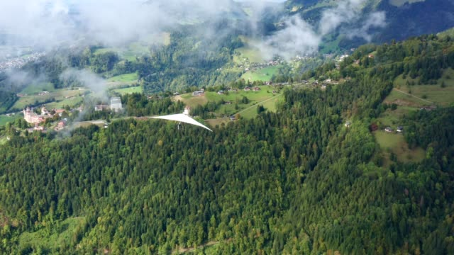 Drone flying behind a hang glider in a picturesque place in Switzerland