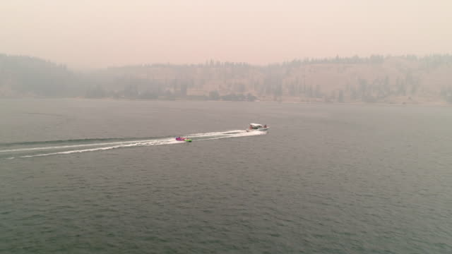Drone Flying Behind Boat Towing Inner Tubes in Eastern Washington Wildfire Haze video