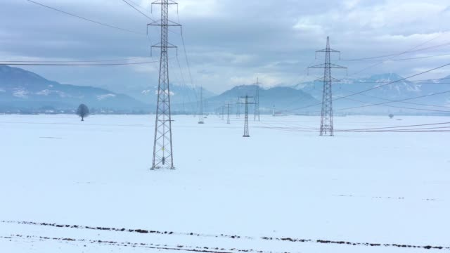 Drone flying between electrical towers on a cloudy day Aerial view with drone flying between wires of big electrical towers on a cloudy winter field landscape covered with white cold snow high voltage sign stock videos & royalty-free footage