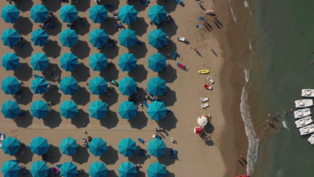 drohne fliegen die strandküste mit dem wasser auf der rechten seite und blue beach regenschirme und strandbesucher auf der linken seite - sonnenschirm stock-videos und b-roll-filmmaterial