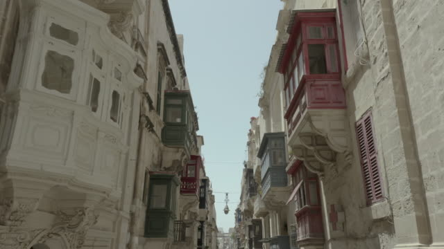 Drone flying forward lifting up on narrow beautiful old street, Valletta, Malta. White car drives off. Vintage balconies. 4K