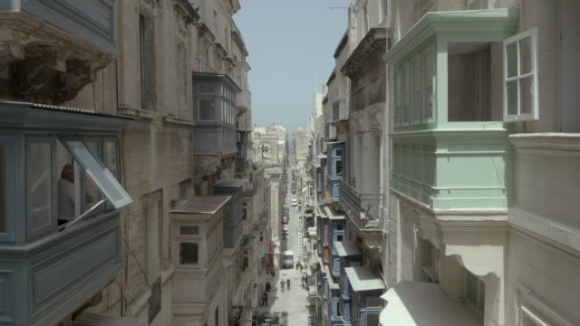 Drone flying forward on narrow beautiful old street,Valletta,Malta . Old, vintage windows, balconies. - 4K