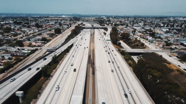 Drone flying forward over large busy American interstate highway with bridges and flyovers, cars move in all directions.