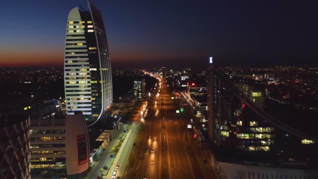 drone flying forward passing modern buildings towers, above busy traffic road - bułgaria filmów i materiałów b-roll