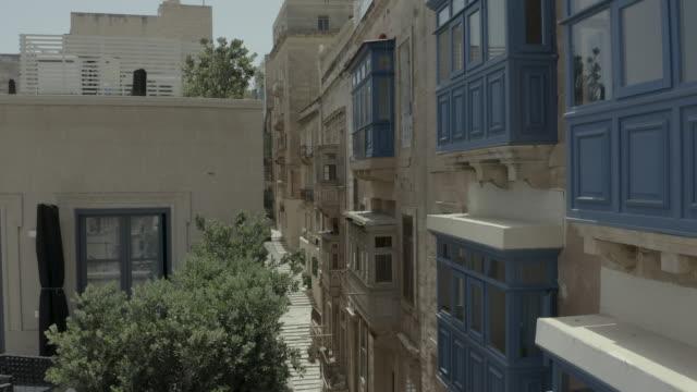 vídeos de stock, filmes e b-roll de zangão que voa para a frente através da rua velha bonita, valletta, malta. velho, janelas vintage, varandas. -4k - estreito mar