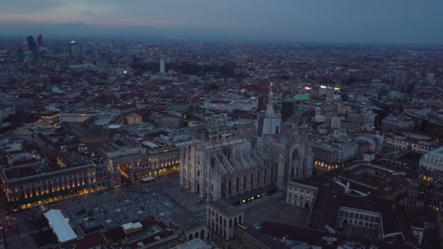 Drone flying forward to Milan Cathedral at night