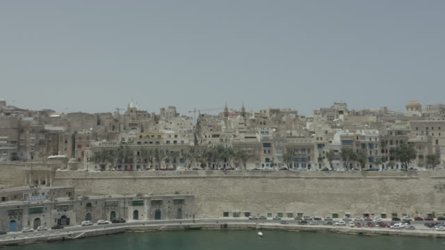 Drone flying from the sea to old city Valletta, Malta island. Old, vintage windows, balconies. Amazing view from above.