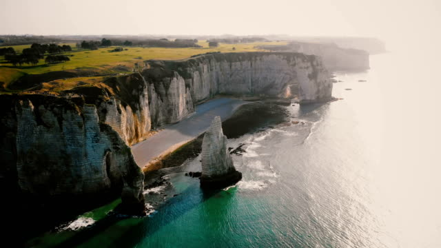 Drone flying high above epic natural rocky arch and pillar at famous white chalk seaside cliffs of Etretat Normandy. Drone flying high above epic natural rocky arch and pillar at famous white chalk seaside cliffs of Etretat Normandy. Cinematic aerial shot of amazing sunset backlit rocks and azure water bay. normandy stock videos & royalty-free footage