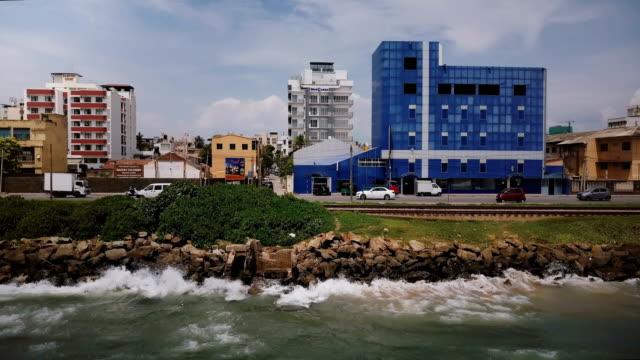 vídeos de stock e filmes b-roll de drone flying left along ocean shore street in colombo, sri lanka. aerial tracking shot of asian resort town sea coast - sri lanka