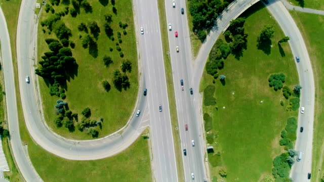 Drone flying looking down bird's eye view of a big city highway with moving cars video