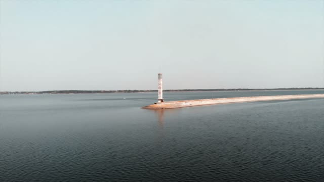 Drone flying near water-power station with lighthouse. Aerial view of calm lake with blue water