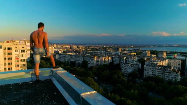 drönare som flyger över en man som står vid kanten på en byggnad tak - på gränsen bildbanksvideor och videomaterial från bakom kulisserna