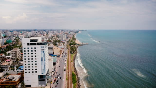Drone flying over beautiful coastline of Colombo, Sri Lanka. Amazing aerial view of busy city street and ocean waves Drone flying over beautiful coastline of Colombo, Sri Lanka. Amazing aerial view of busy city street and ocean waves, city buildings and cloudy sky. Street traffic, modern architecture at seaside. colombo stock videos & royalty-free footage