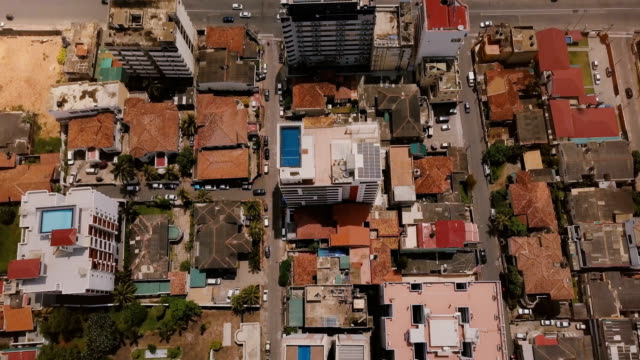 Drone flying over buildings of Colombo, Sri Lanka towards seashore. Aerial top view of Asian resort town and ocean Drone flying over buildings of Colombo, Sri Lanka towards seashore. Aerial top view of Asian resort town buildings, busy street and ocean. Beautiful top view of small houses, modern hotels, coastline. colombo stock videos & royalty-free footage