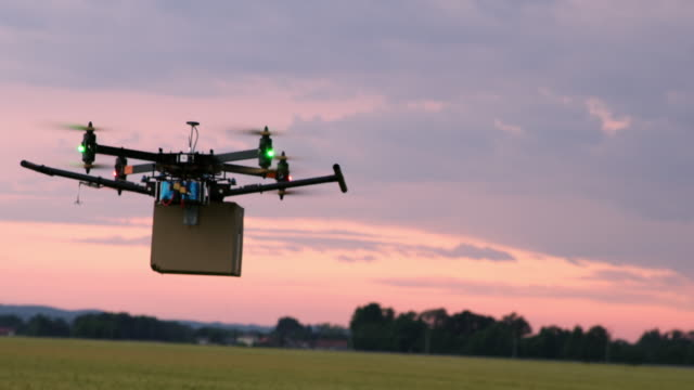 LS Drone flying over fields with a package at dusk Long shot of a drone flying over fields while carrying a package. Shot was taken at dusk. cultivated land stock videos & royalty-free footage
