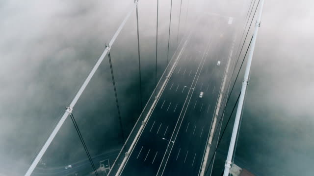 drone flying over foggy bridge at sunrise in istanbul - stambuł filmów i materiałów b-roll