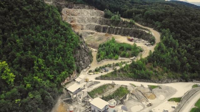 vídeos de stock e filmes b-roll de drone flying over open pit mine/quarry - triturar atividade