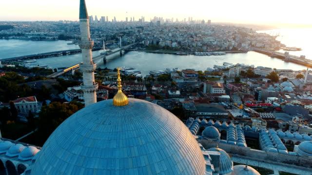 vídeos y material grabado en eventos de stock de drone volando sobre el puente domo y metro de la mezquita de suleymaniye en el cuerno de oro de estambul al amanecer - distrito eminonu